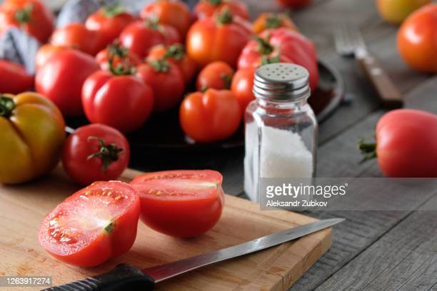 ripe red tomatoes on a wooden table. vegetarian, vegan, and raw food. organic homemade farm products. - sal de cozinha - fotografias e filmes do acervo