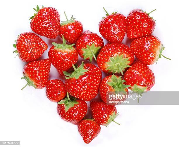 ripe strawberries laying in a heart shape - aardbei stockfoto's en -beelden