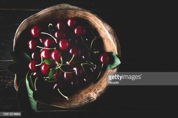 reife süßkirsche in holzschale auf dunklem hintergrund - kirsche stock-fotos und bilder