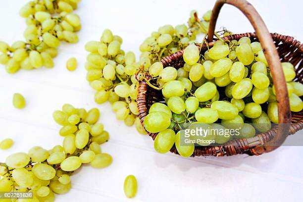 Ripe white grapes on white.