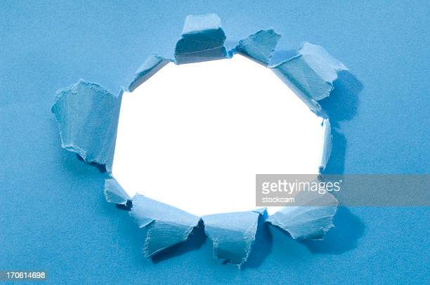 ripped hole in a blank blue paper - appearance stock photos and pictures