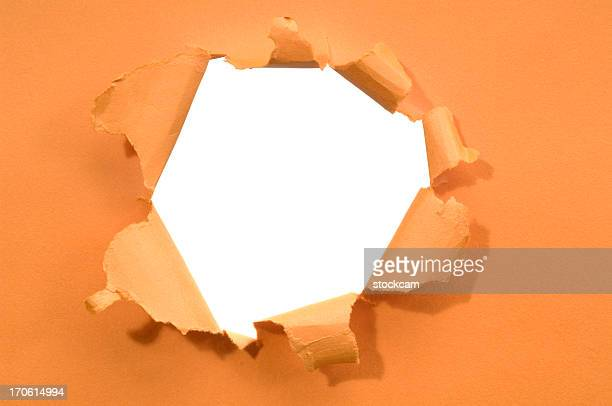 Ripped hole in a paper isolated on white