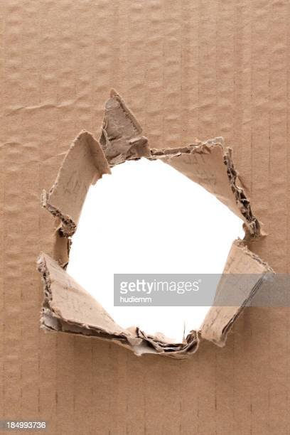 Ripped hole in cardboard background textured