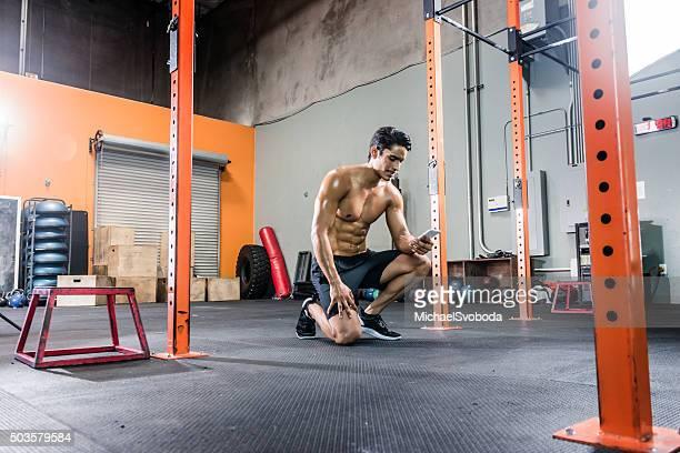 Zerrissene Mann, die seinem Smartphone im Fitnessstudio.