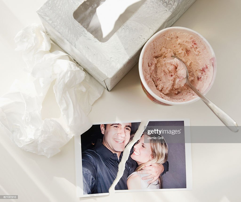 Ripped photograph next to ice cream and tissues : Stock Photo