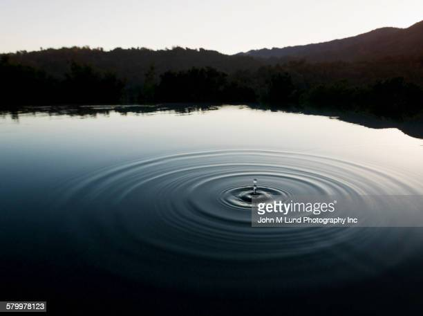 Ripple of water in still lake near mountains