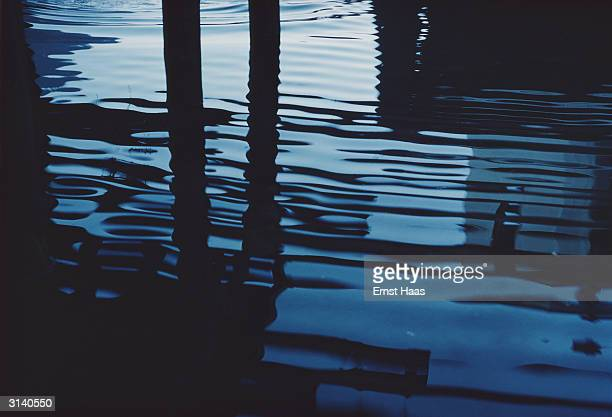 Ripples on the surface of a canal in Venice where a pair of stilts disappear into the water Colour Photography book