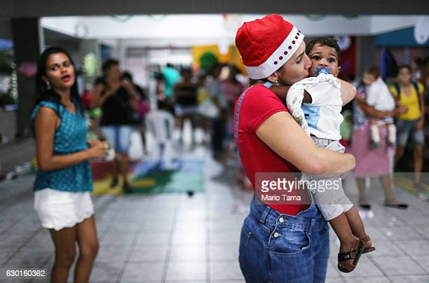 Riquelme Kauan who was born with microcephaly is embraced by a caregiver as his mother Avila looks on during a Christmas party on December 17 2016 in...