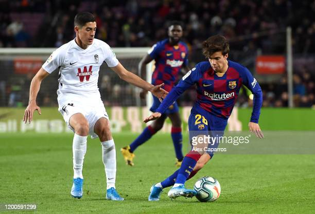 Riqui Puig of FC Barcelona is challenged by Carlos Fernandez of Granada CF during the La Liga match between FC Barcelona and Granada CF at Camp Nou...
