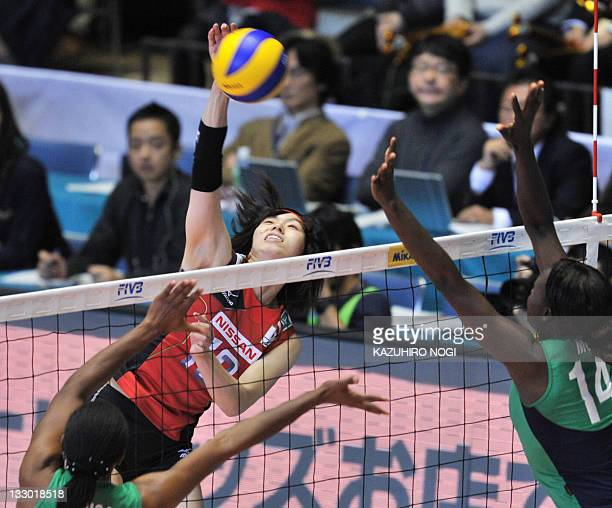 Risa Shinnabe of Japan spikes the ball over Diana Khisa and Mercy Moim of Kenya during a match of the World Cup women's volleyball tournament in...