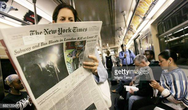 Risa Turken reads The New York Times with an article about the London terror attacks while riding the subway during the morning rush hour July 8 2005...