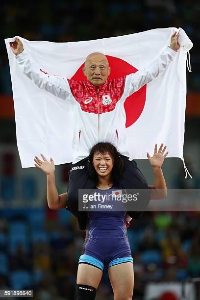 Risako Kawai of Japan celebrates with her coach Kazuhito Sakae after defeating Maryia Mamashuk of Belarus during the Women's Freestyle 63 kg Gold...