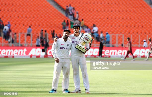 Rishabh Pant and Axar Patel of India pose for a photo with the trophy after victory on Day Three of the 4th Test Match between India and England at...