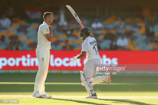 Rishabh Pant of India celebrate victory while Josh Hazlewood of Australia looks on during day five of the 4th Test Match in the series between...
