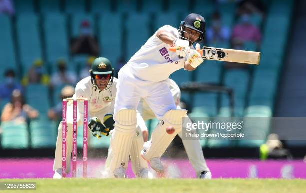 Rishabh Pant of India hits out watched by Tim Paine of Australia during day five of the Test match in the series between Australia and India at...