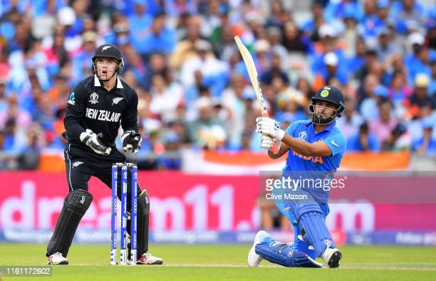 Rishabh Pant of India is caught by Colin de Grandhomme of New Zealand off the bowling Mitchell Santner during resumption of the SemiFinal match of...