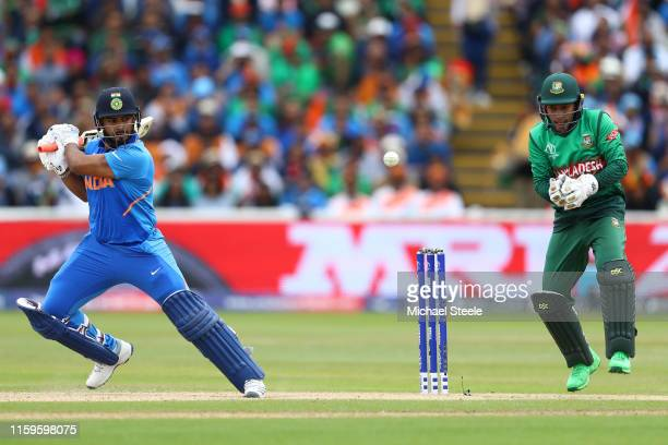 Rishabh Pant of India plays to the offside as Bangladesh wicketkeeper Mushfiqur Rahim looks on during the Group Stage match of the ICC Cricket World...