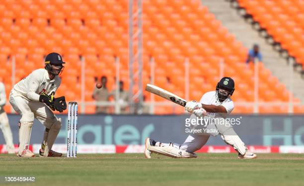 Rishabh Pant of India sweeps watched on by Ben Foakes of England during Day Two of the 4th Test Match between India and England at Sardar Patel...