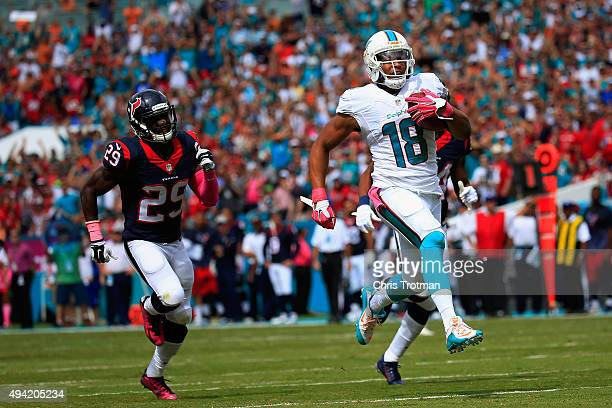Rishard Matthews of the Miami Dolphins runs the ball back for a touchdown in the first quarter as Andre Hal of the Houston Texans looks on during a...