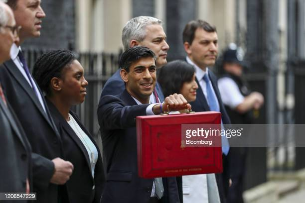 Rishi Sunak UK chancellor of the exchequer fourth left holds a dispatch box as he poses for a photographer with left to right Theodore Agnew minister...