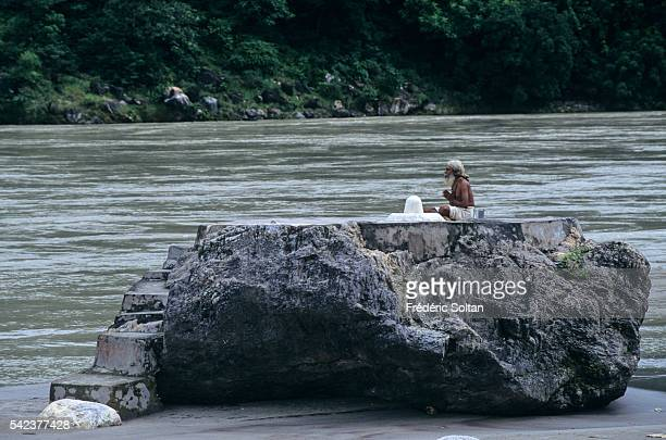 Rishikesh located in the foothills of Himalaya is an important center of pilgrimage for Hindus A Sadhu is praying near a lingam symbol for the...