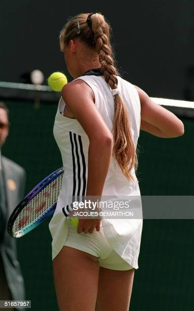 Rising Russian tennis star Anna Kournikova keeps one ball busy while finding a storage space for another as she prepares to serve during her opening...