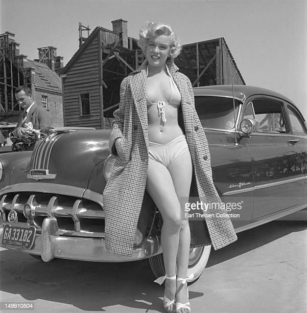 Rising star Marilyn Monroe poses for a portrait next to a 1950 Pontiac Chieftain on the backlot of 20th Century-Fox in 1951 in Los Angeles,...