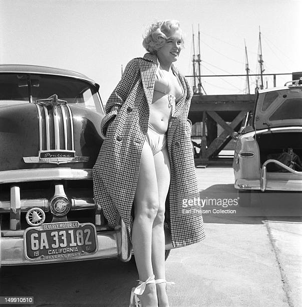 Rising star Marilyn Monroe poses for a portrait next to a 1950 Pontiac Chieftain on the backlot of 20th CenturyFox in 1951 in Los Angeles California