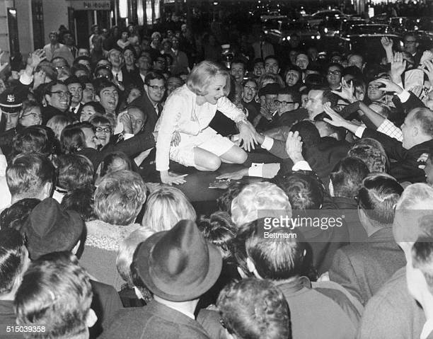 That creator of legends Marlene Dietrich happily climbs atop her waiting limousine as protection from wildly enthusiastic fans outside the...