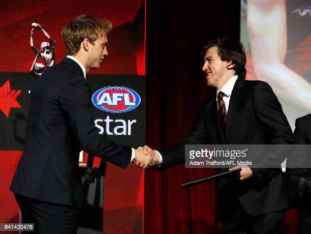 Rising star winner Andrew McGrath of the Bombers is presented his medal by last years winner Callum Mills of the Swans during the 2017 NAB AFL Rising...