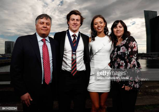 Rising star winner Andrew McGrath of the Bombers poses for a photo with parents Michael and Sandy McGrath and partner Tilly Jackson during the 2017...