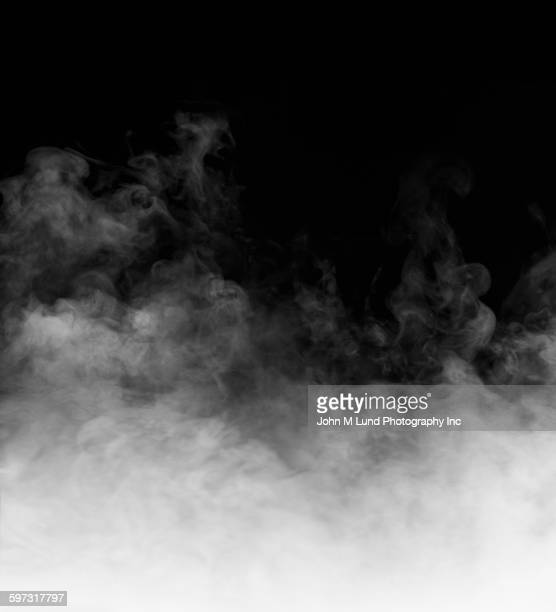 rising steam on black background - nebel stock-fotos und bilder