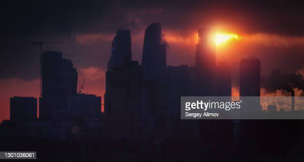 rising sun behind skyscrapers of dark city skyline - blackout stock pictures, royalty-free photos & images