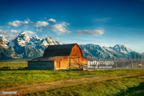 a rising sun illuminates the john moulton homestead's barn and corrals with the magnificent tetons as a backdrop. - ranch stock pictures, royalty-free photos & images