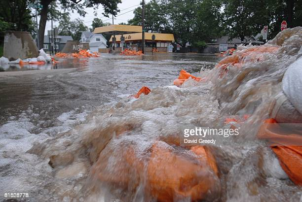 Rising water rushes out of sewer drains in low lying areas on June 11, 2008 Cedar Rapids, Iowa. Several areas of the city have already been...