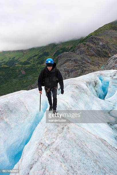 Risky walk between crevasses on icy glacier