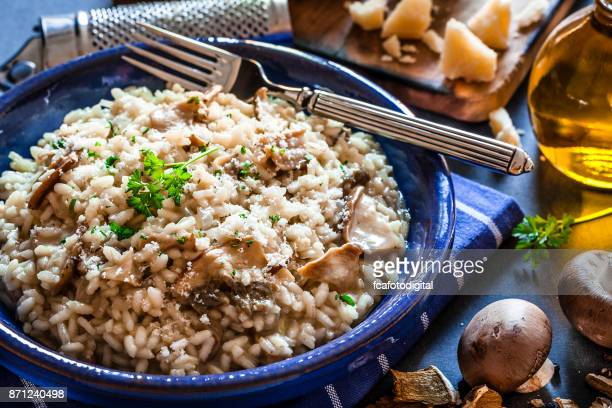 Risotto fungi porcini on dark kitchen table