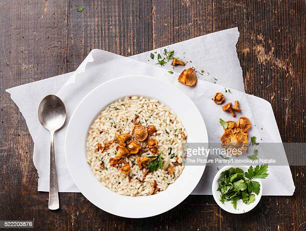 Risotto with chanterelles on wooden table