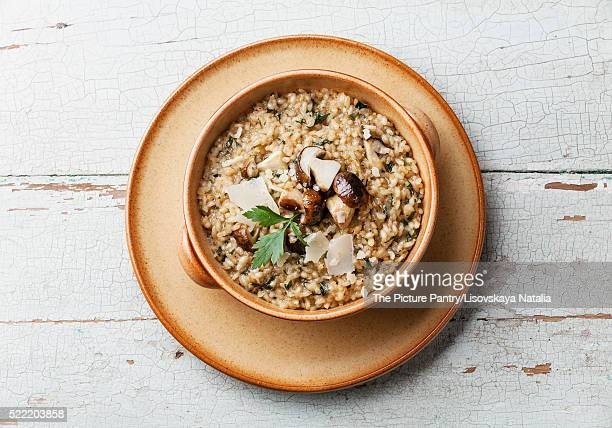 Risotto with wild mushrooms with parsley and parmesan on blue ba