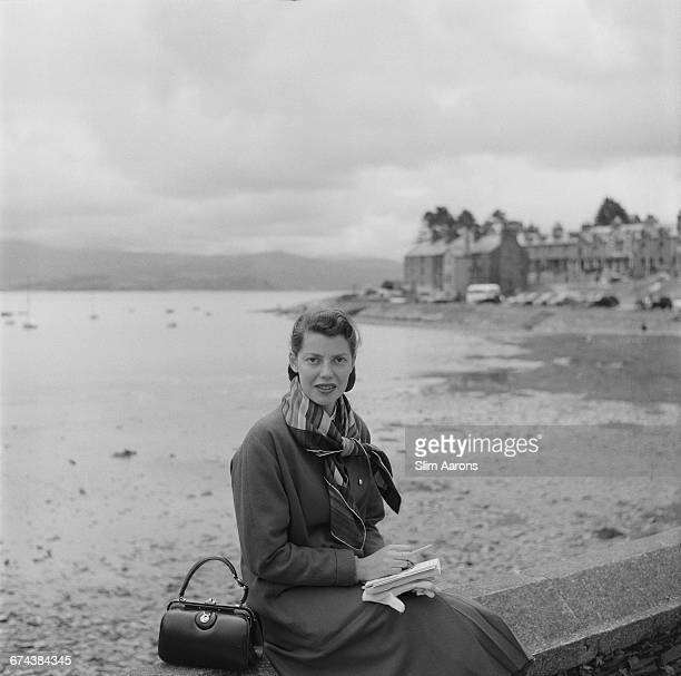 Rita Aarons wife of photographer Slim Aarons poses on a beach in Wales 1957