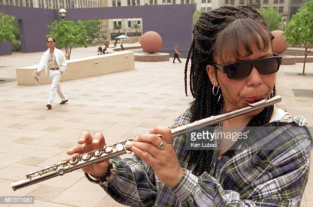 Rita Barker a general relief recipient plays her flute in Pershing Square hoping that coins will be polaced in her flute case by appreciative...