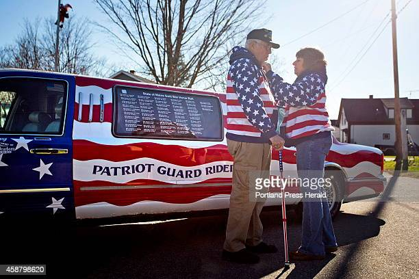 Rita Dearborn fusses over her husband's American flag sweatshirt as they stand in front of his 1997 Lincoln Town Car Limousine that they drive around...