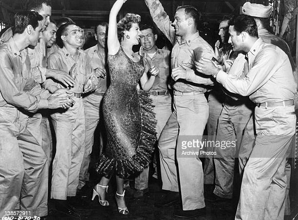 Rita Hayworth and Aldo Ray dancing as a crowd of military men cheer them on in a scene from the film 'Miss Sadie Thompson' 1953