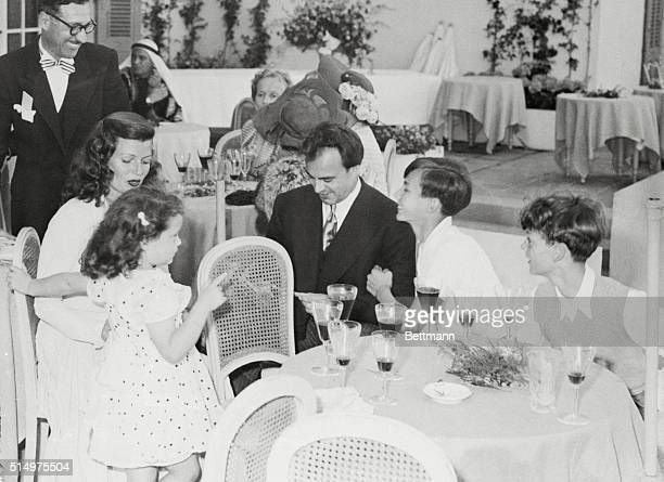 Rita Hayworth and her new husband are shown as they caught their breaths during a lull in the festivities that followed their wedding Friday Prince...