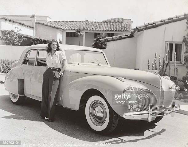 Rita Hayworth photographed in front of her bungalow which she occupied while appearing in Columbia Pictures' You'll Never Get Rich She is leaning...