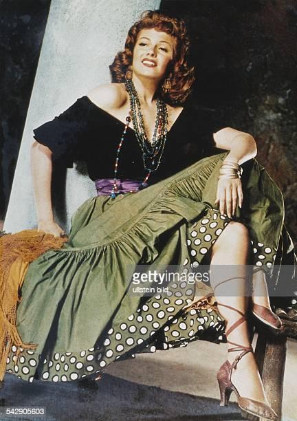 Rita Hayworth sitzt mit übereinander geschlagenen Beinen auf einer Stufe Sie trägt einen weiten Stufenrock dessen Saum gepunktet ist Dazu trägt sie...