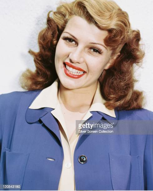 Rita Hayworth US actress and dancer wearing a blue jacket and white blouse smiling in a studio portrait against a white background circa 1950