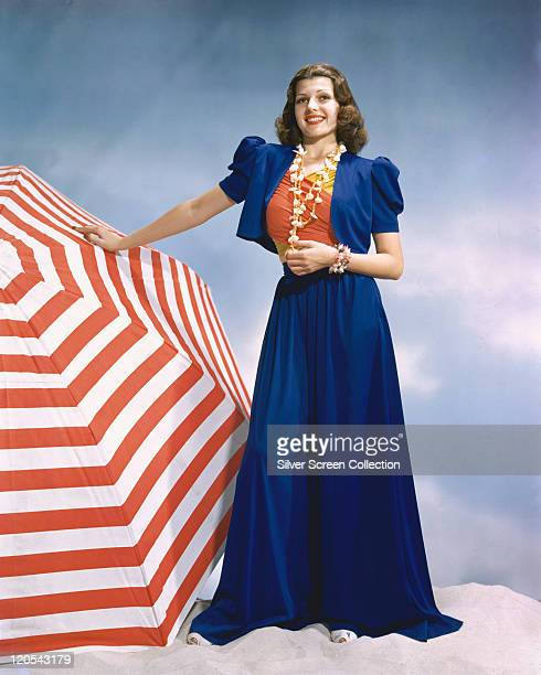 Rita Hayworth US actress and dancer wearing a long blue skirt and a matching blue jacket with a redandyellow top with a shell necklace around her...
