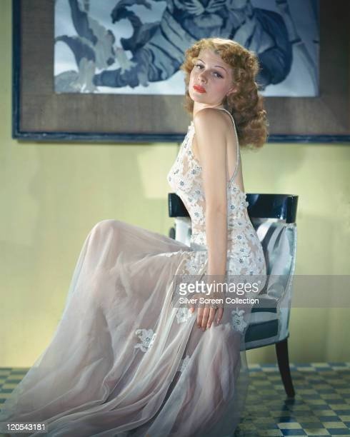 Rita Hayworth US actress and dancer wearing a long dress with a white lace bodice with floral motifs and a white chiffon skirt sitting in a chair in...