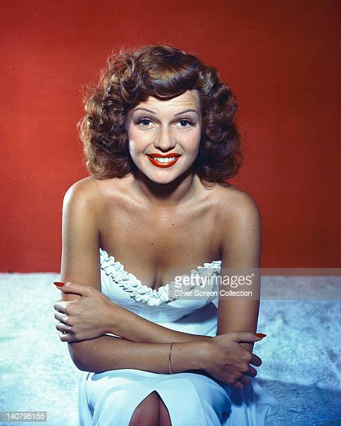 Rita Hayworth US actress and dancer wearing a white shoulderless dress and smiling in a studio portrait against a red background circa 1950